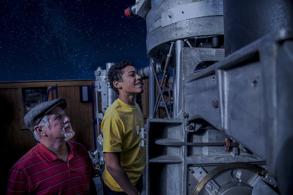 Student looking through telescope with Dr. Faulkner